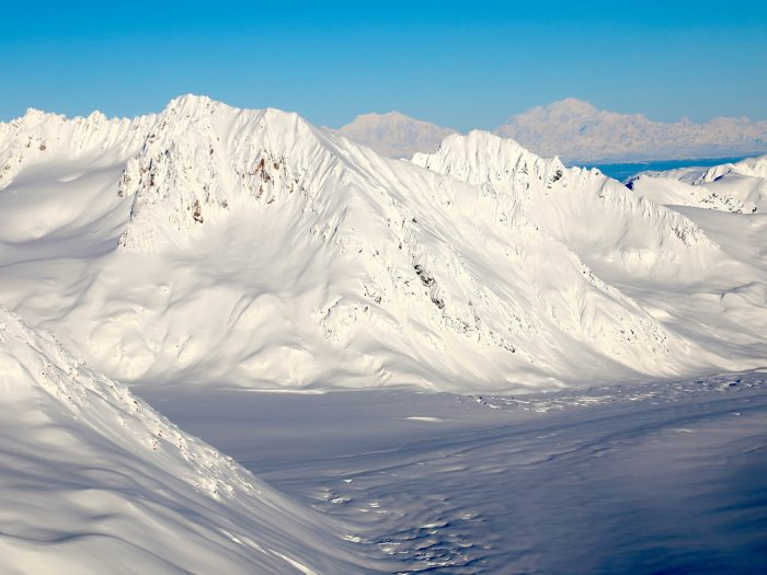 View of high mountain peaks in Alaska covered with fresh snow on a clear day.
