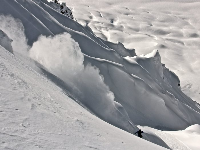 Man skis down an untracked trail of fresh snow while heli skiing in the Tordrillo Mountains of Alaska.