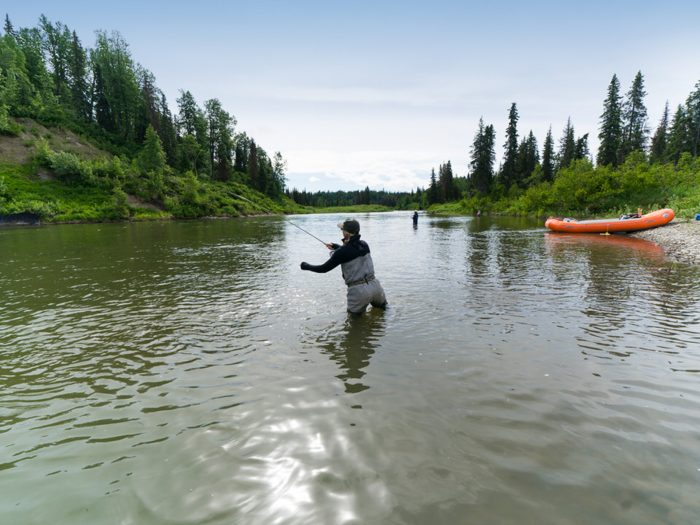 Female angler throws a fishing line into a flowing creek in Alaska on a Kings and Corn summer excursion.