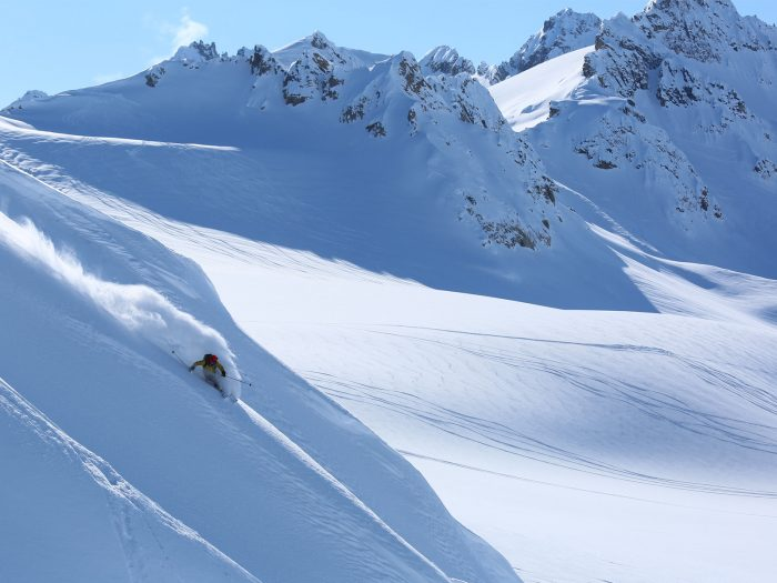Male skier slides down a mountain in Alaska with fresh powdery snow.