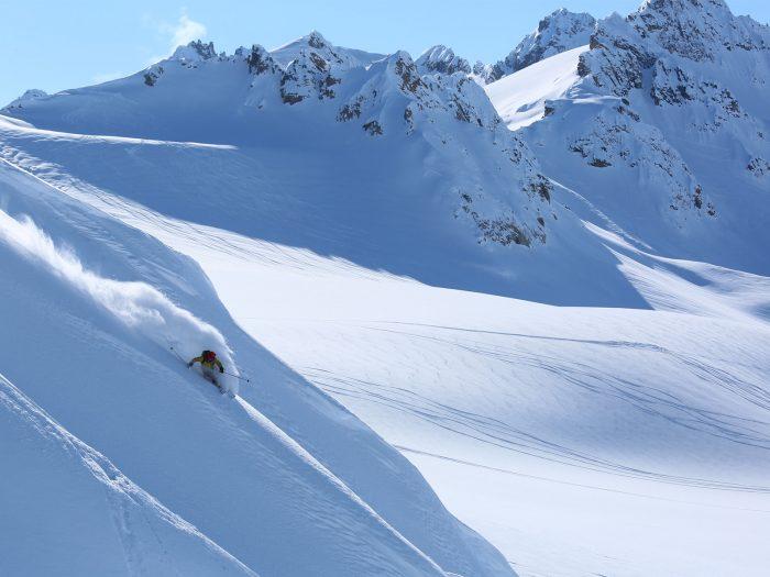 Male skier slides down a mountain in Alaska with fresh powdery snow.