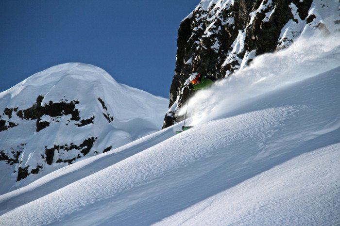 Skier in a lime green jacket skis down a mountain in Alaska with a fresh layer of powdery snow.