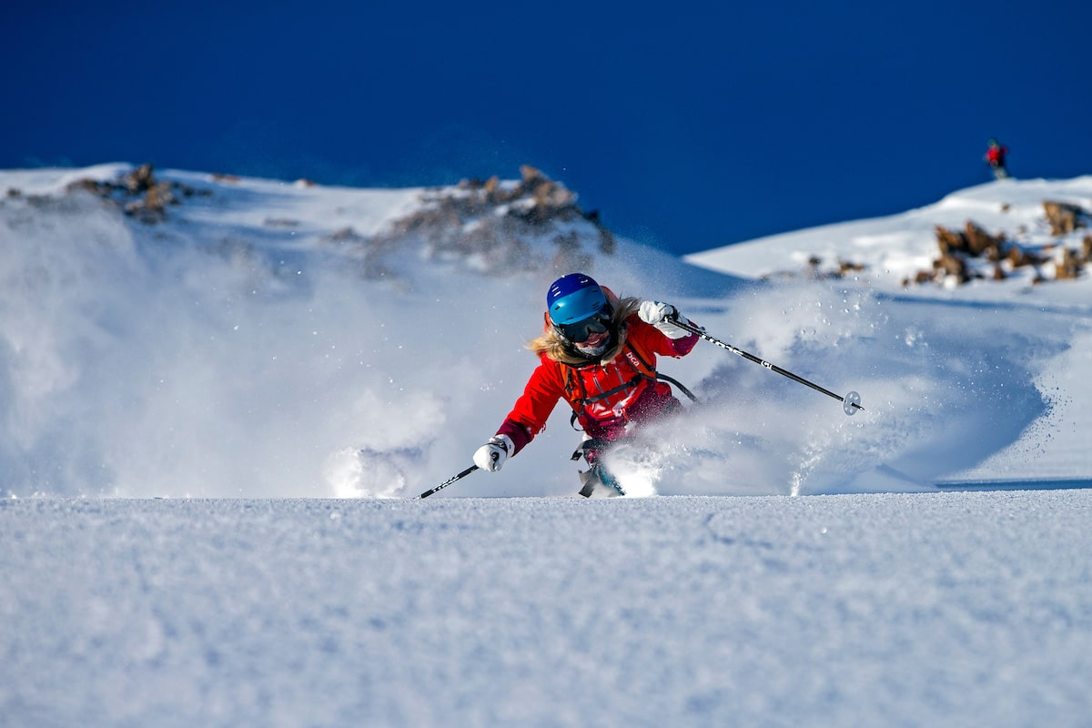 A female skier wearing a red jacket and blue helmet heli skis down the Tordrillo Mountains in Alaska.