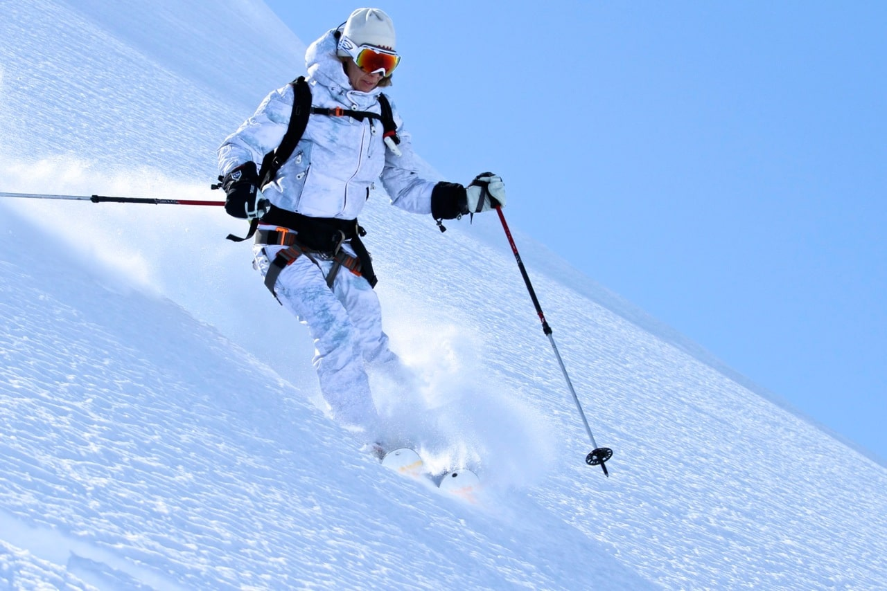 Female skier wearing a white snow suit heli skis down a snow covered mountain with Tordrillo Mountain Lodge in Alaska.