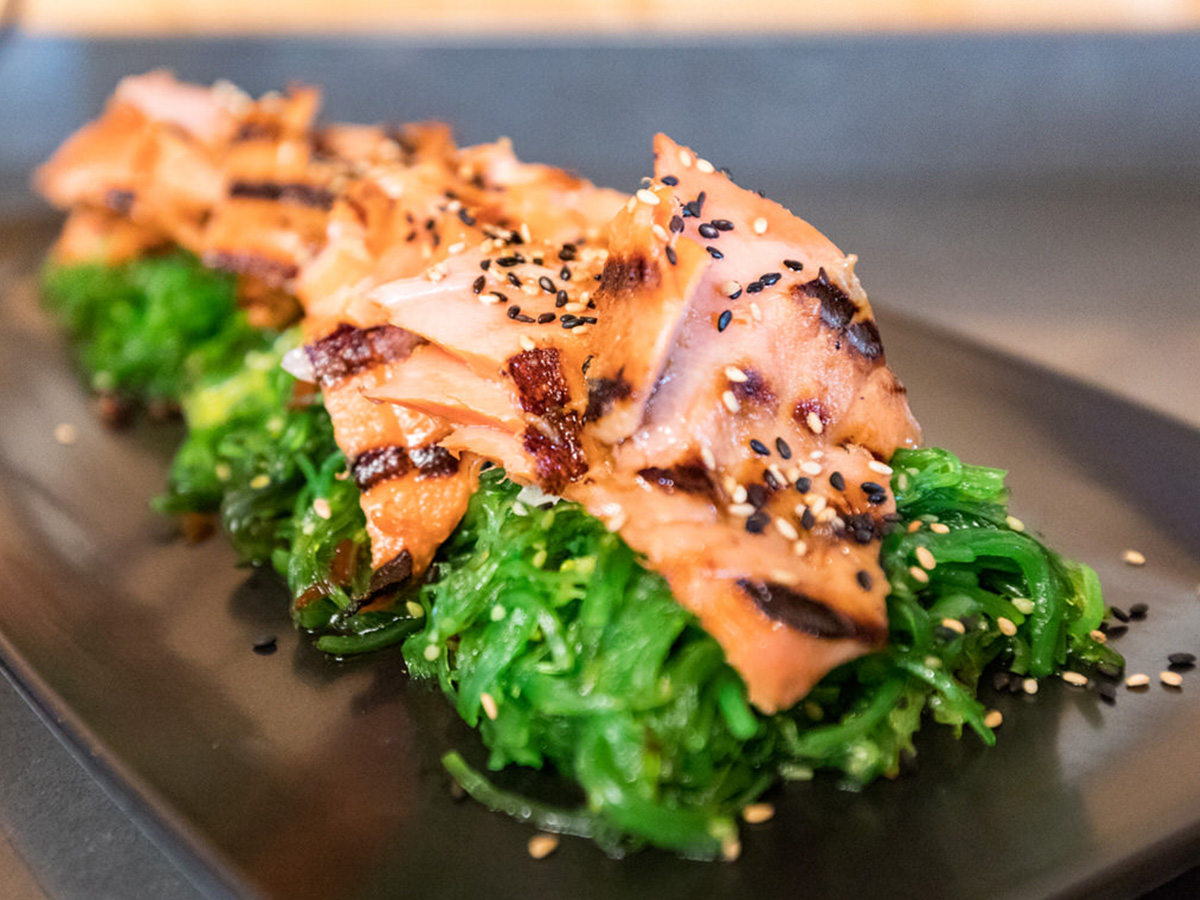A close up of a plate of Alaska salmon on a bed of greens.