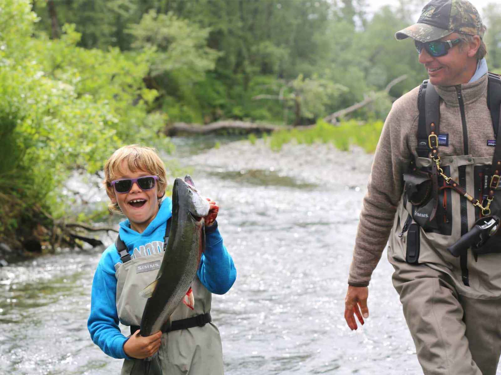 Father and son fishing in an Alaskan river with the son holding a fish they caught.
