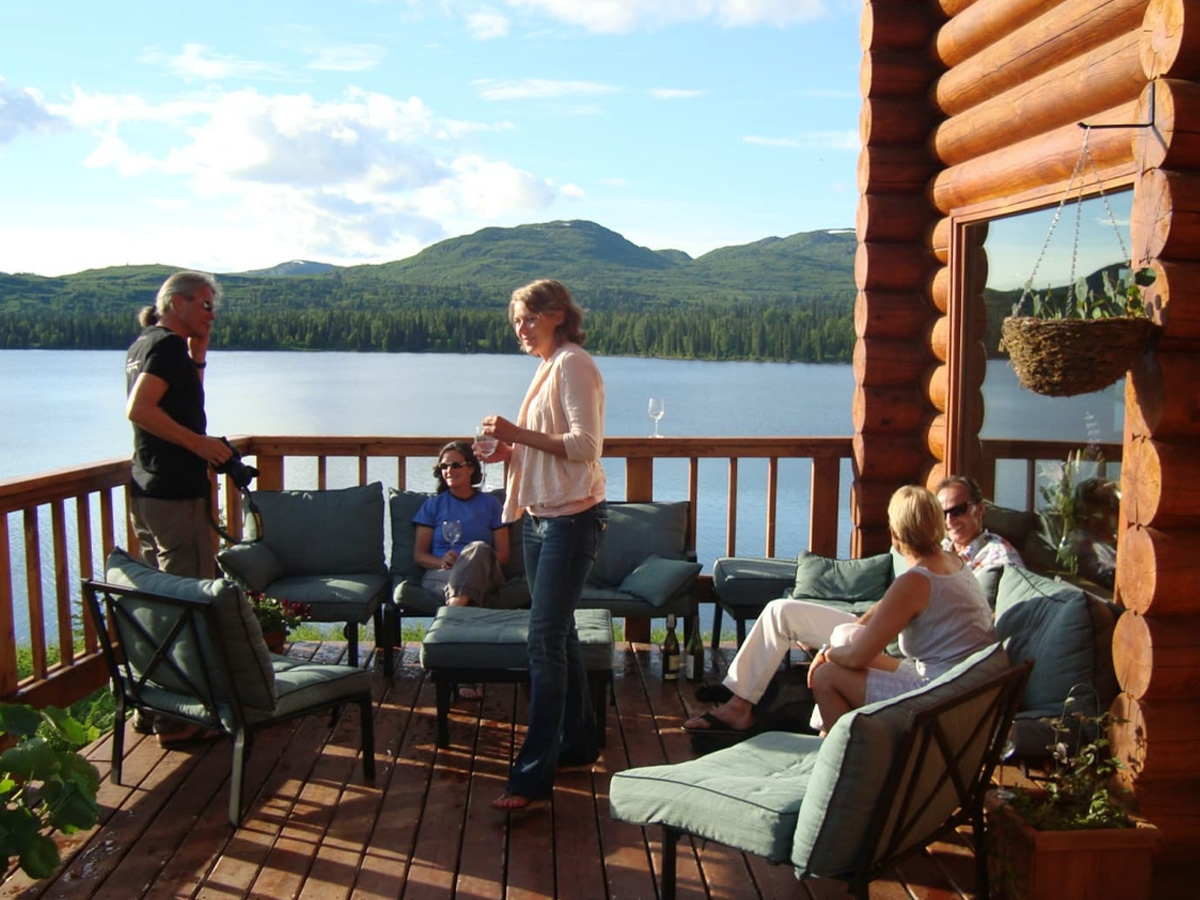 A family enjoying time on the Tordrillo Mountain Lodge balcony on a warm summer day.