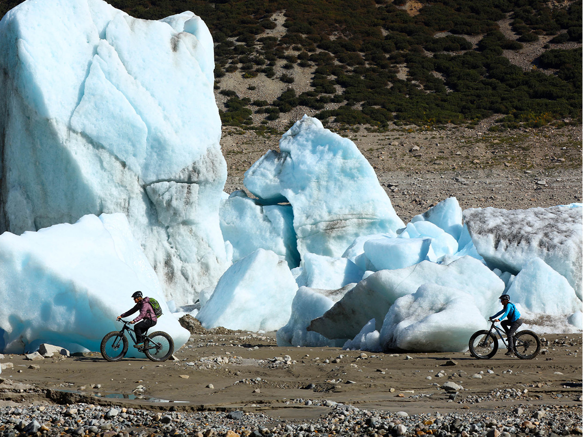 Two people heli biking in Alaska next to large glaciers.