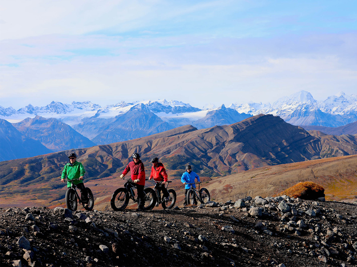 Four people riding fat bikes in the Tordrillo Mountain Range.