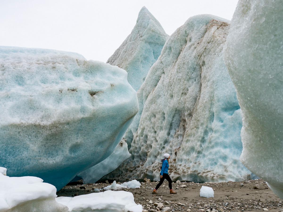 Women hiking in Alaska next to very tall glaciers.