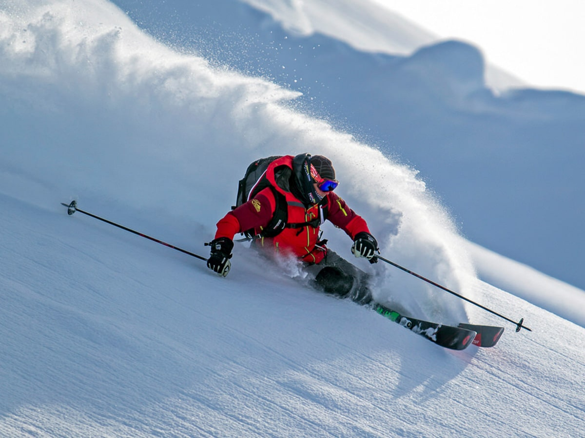 A skier carves down a mountain after being dropped by helicopter in the Tordrillo Mountains.