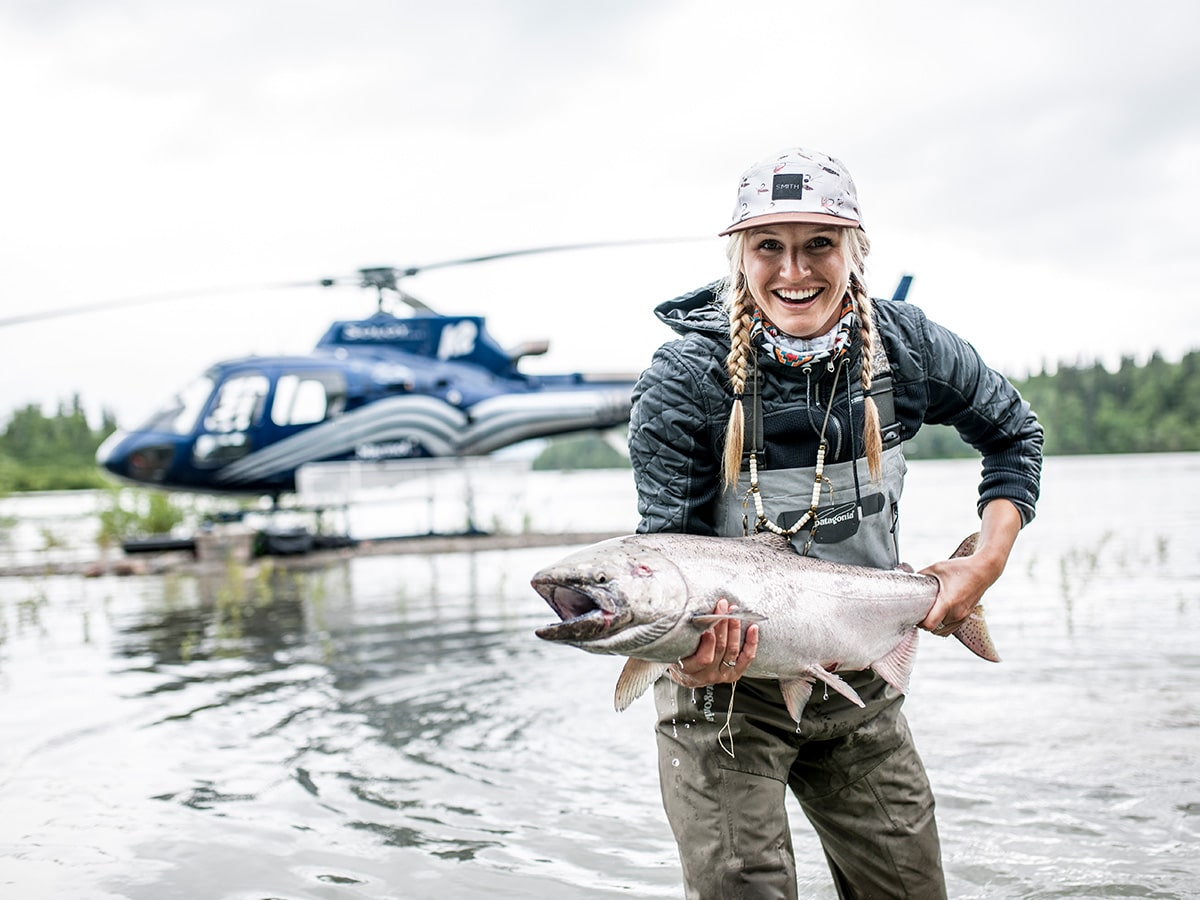 A woman holds a fish she caught during a day of heli fishing with a helicopter behind her.