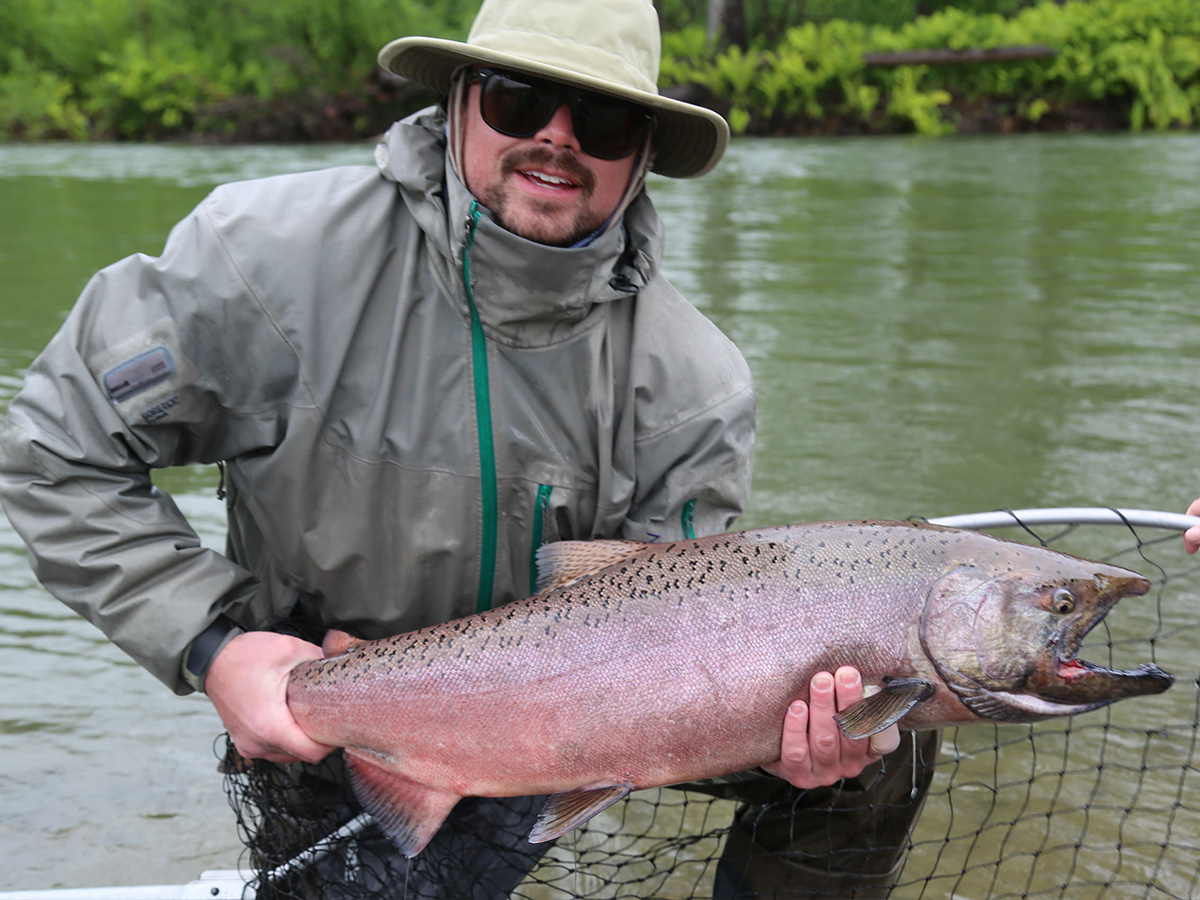 Man holding a large Alaskan King salmon they just caught over a net.