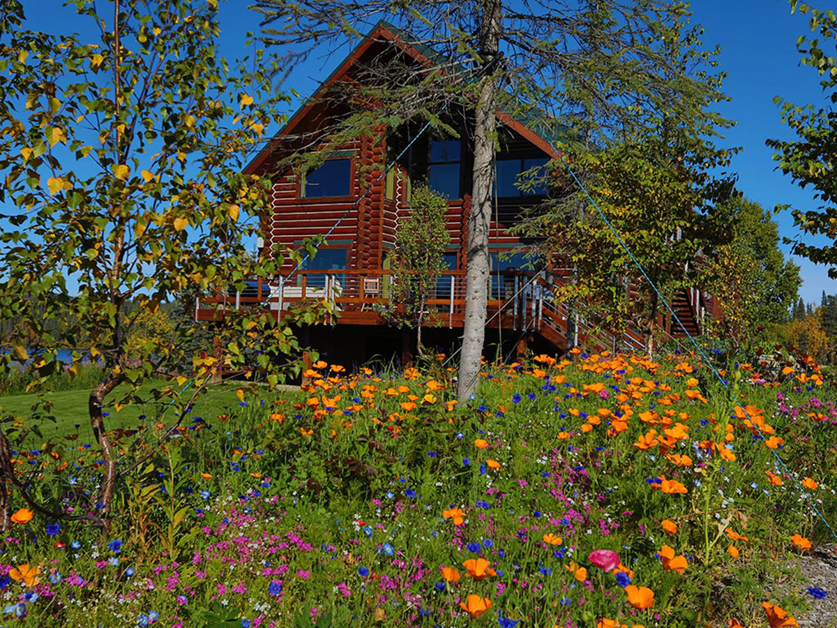 Outdoor view of the Tordrillo Mountain Main Lodge in Spring with flowers everywhere.
