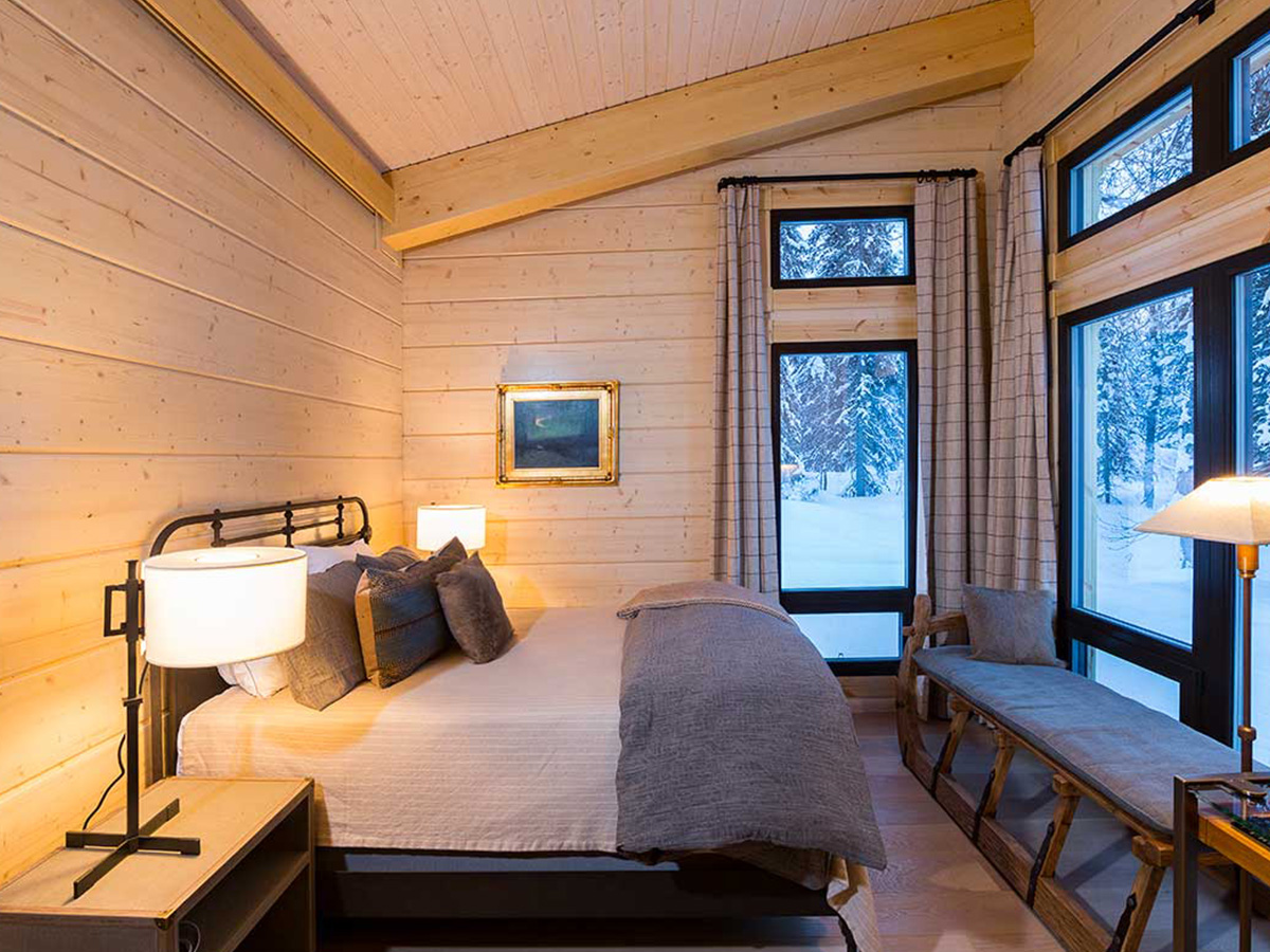 Moose Hall & Lakeside Retreats bedroom with a large bed and windows with a view of snow.
