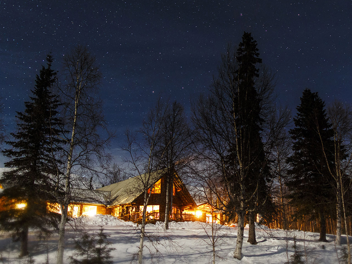 Exterior view of Winterlake Lodge at night with stars in the sky.