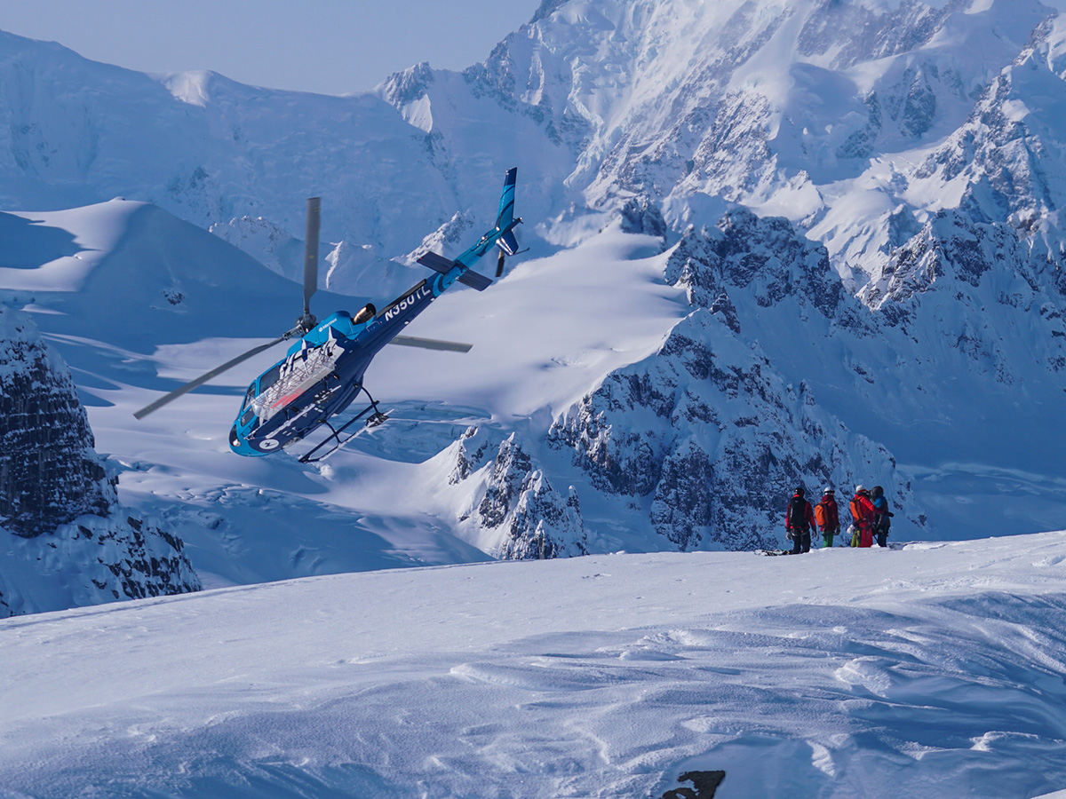 A helicopter drops off skiiers on a sunny winter day in the Alaskan backcountry.