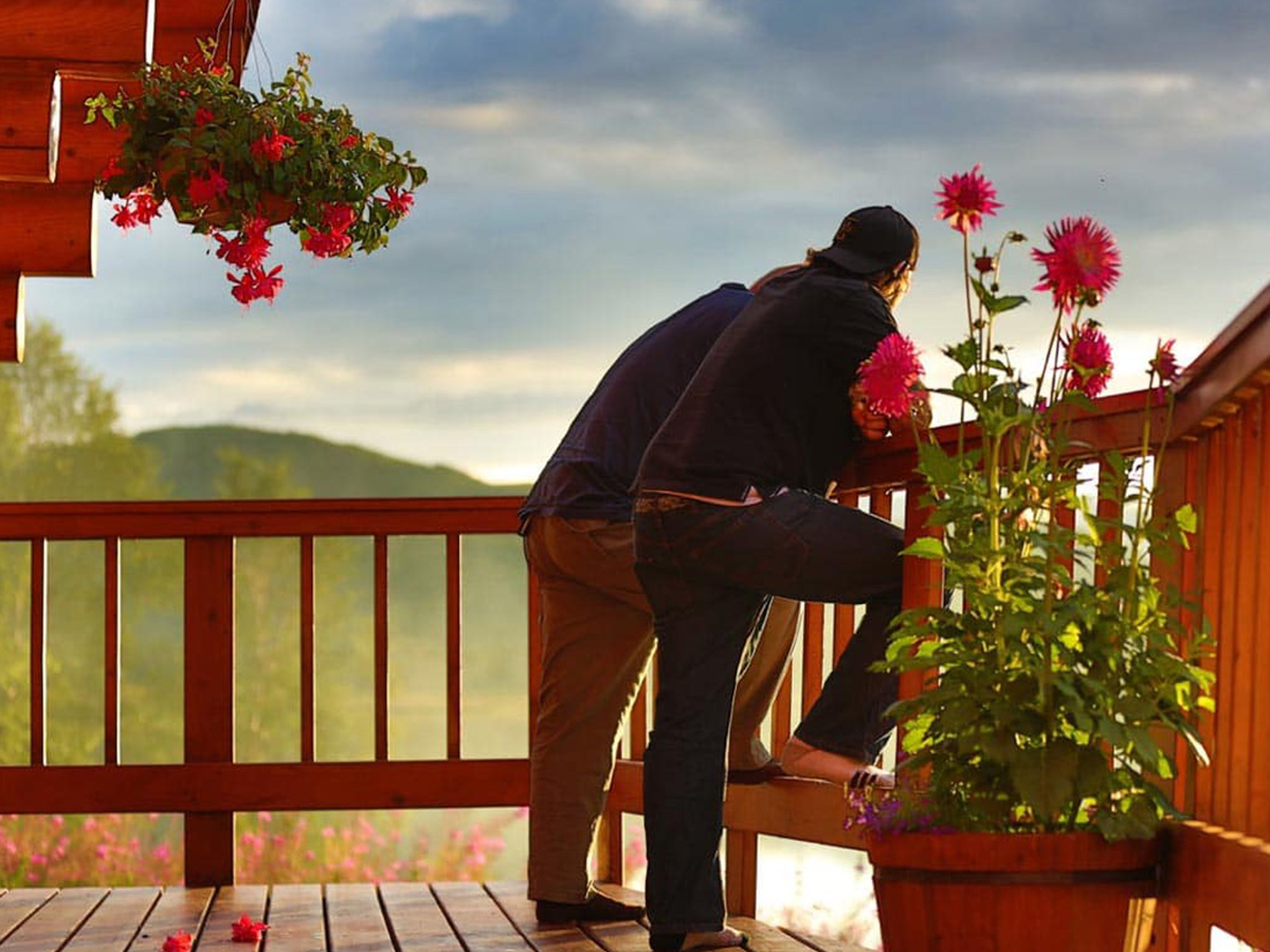 Two men standing outside on the Tordrillo Mountain Lodge balcony on a sunny day.