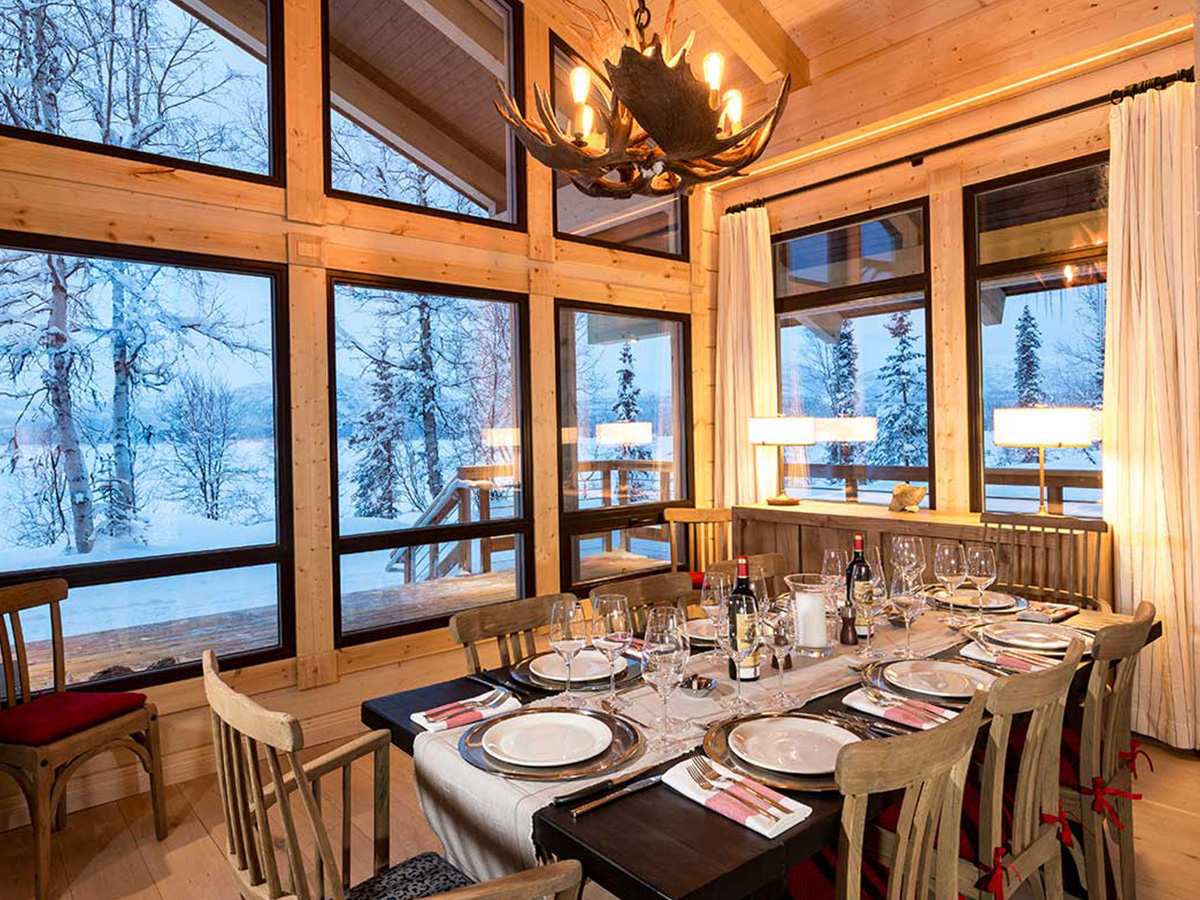 Mouse Hall & Lakeside Retreats dining room table prepared with plates and glasses with a view of snow out the window.