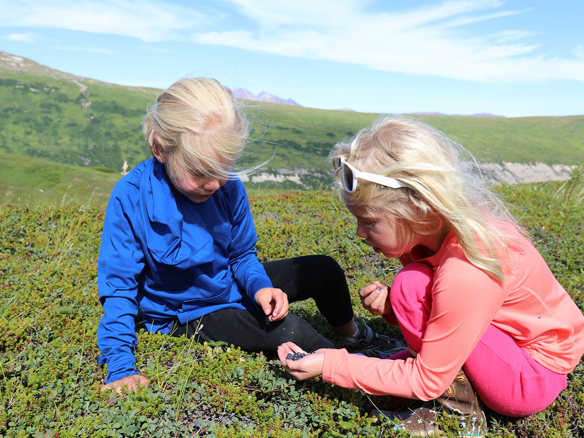 Two young girls playing in the grass in Alaska.