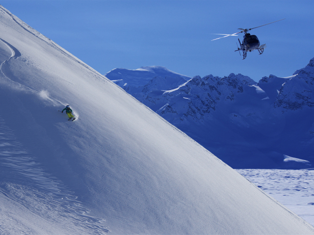 Action photo of a skier going down a steep mountain with a helicopter following close above.