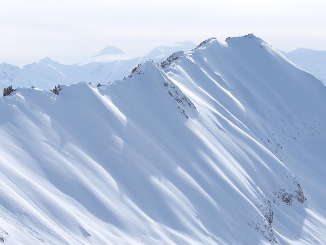A Tordrillo Mountain edge covered in snow with more mountains in the background.