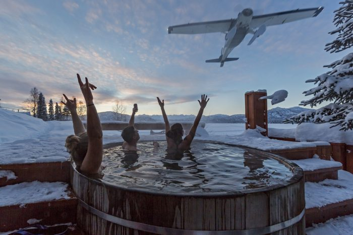 Guests at Tordrillo Mountain Lodge relax in the outdoor copper hot tub after a day of heli skiing.