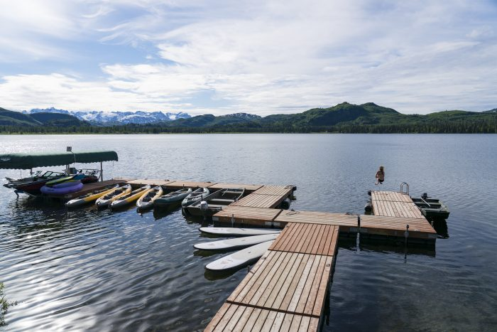 A Tordrillo Mountain Lodge guest cannonballs into Judd Lake during an Alaska vacation.