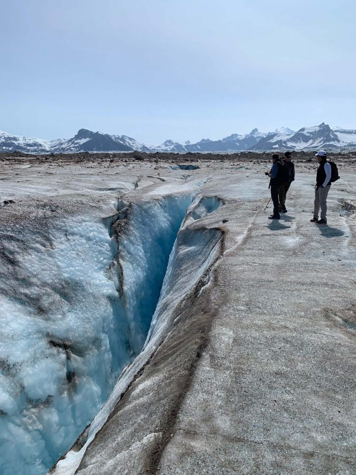Hikers from Tordrillo Mountain Lodge look into the crevasse of an Alaska glacier.