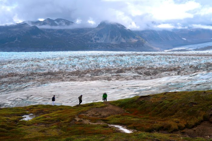 A group of hikers stand on the edge of a glacial field in the Tordrillo Mountains.