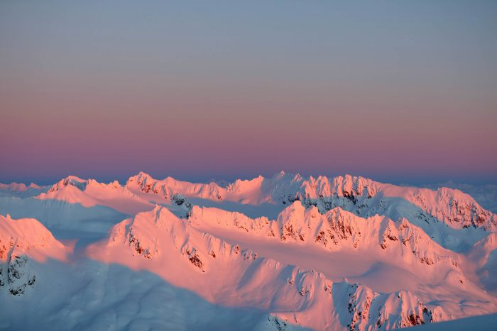 A pink sunset over snow covered Tordrillo Mountains in Alaska.