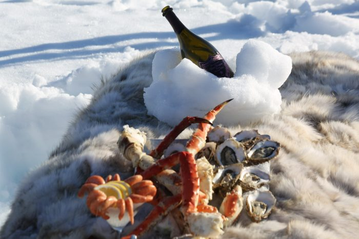 Crab legs and champagne are nestled in snow showing the lap of luxury skiing in Alaska.
