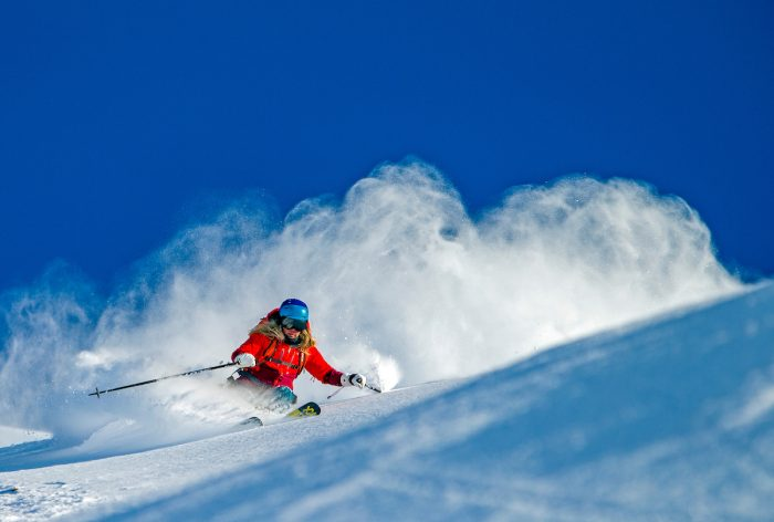 Female skier in a red coat and goggles skis down a mountain of fresh powder.