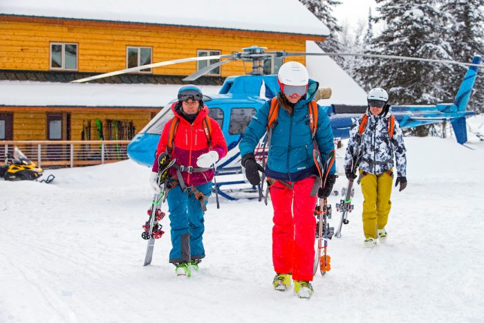 A group of skiers walk away from a helicopter after a day of heli skiing at Tordrillo Mountain Lodge.