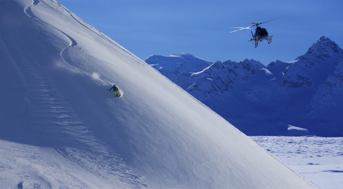 A heli skier makes a run through fresh powder as a helicopter hovers nearby at Tordrillo Mountain Lodge.