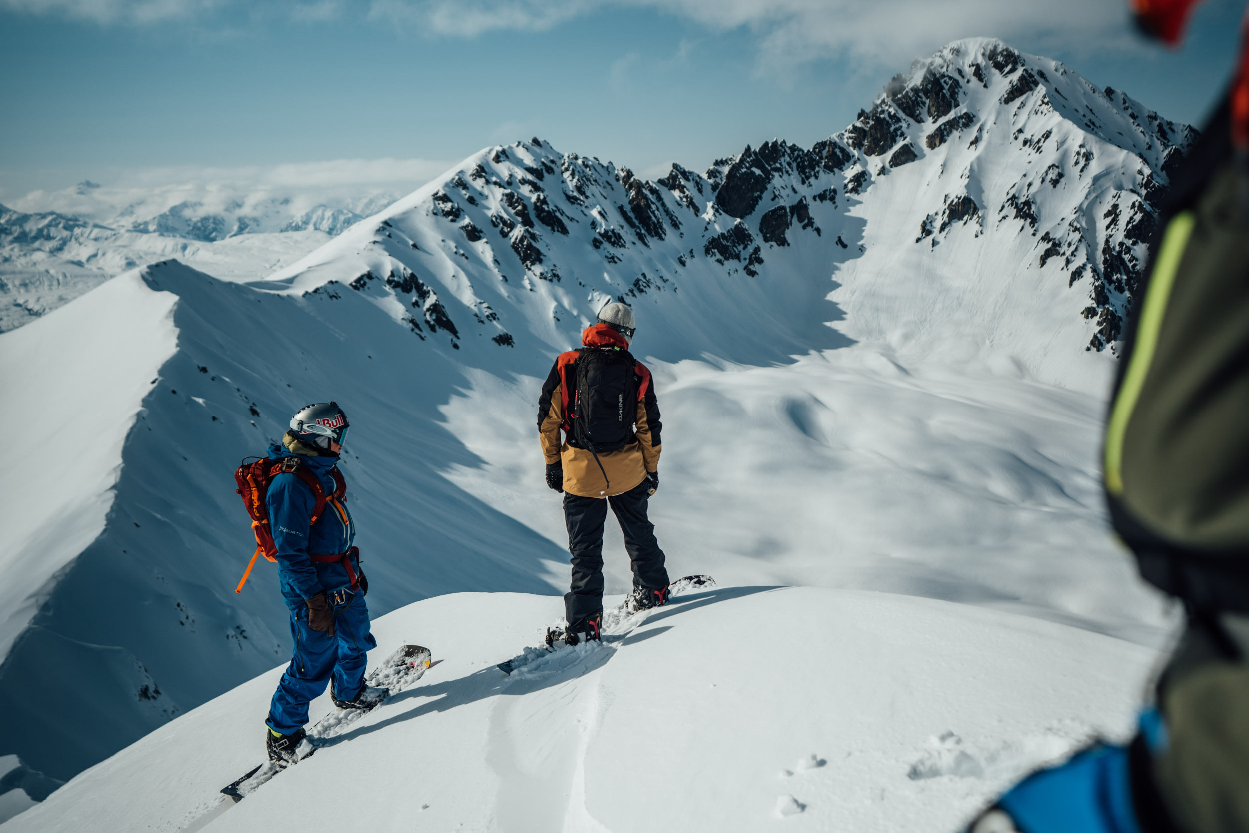 A group of snowboarders take in the view of Tordrillo Mountains in Alaska before snowboarding down a snowy slope.
