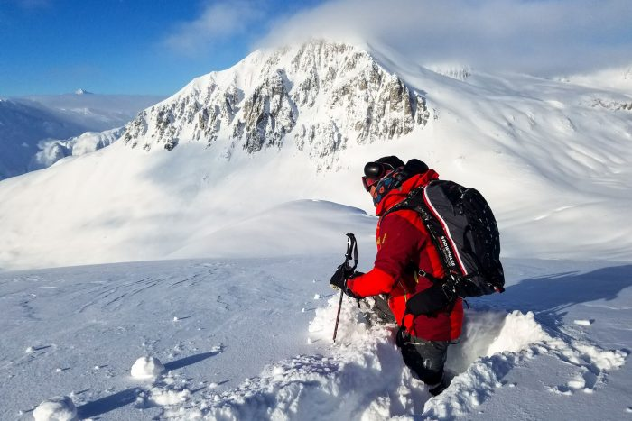 Skier in red coat and black backpack with snow covered mountain in the background.