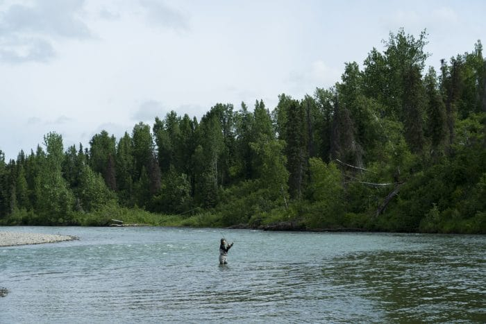 A lone angler fly fishes for salmon on a river near Tordrillo Mountain Lodge.
